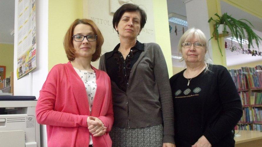 Przed tablicą patrona biblioteki, od lewej – bibliotekarz oddziału dla dzieci, Monika Misiuda, dyrektor Jolanta Banach, kierownik wypożyczalni dla dorosłych, Barbara Jędrzejewska.