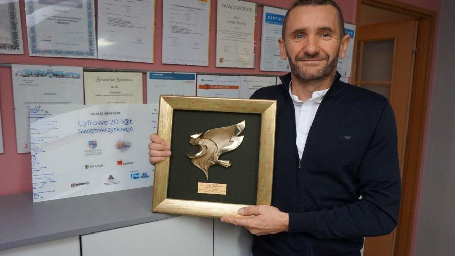 """Fot. Zbigniew Dąbrowski, współwłaściel firm BitNet, prezentuje otrzymaną nagrodę konkursie """"Cyfrowe 20 lat Świętokrzyskiego""""."""